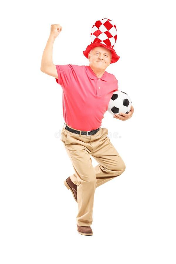 W średnim wieku wielbiciel sportu z kapeluszem trzyma piłkę i gestykuluje happ