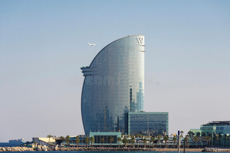 W Barcelona hotel with an airplane flying next to this. Barcelona, Spain - June 1, 2016: The W Barcelona hotel, also known as the hotel vela `sail hotel` royalty free stock photo