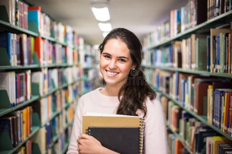 W bibliotece - ładny żeński uczeń z książkami pracuje w h obrazy royalty free