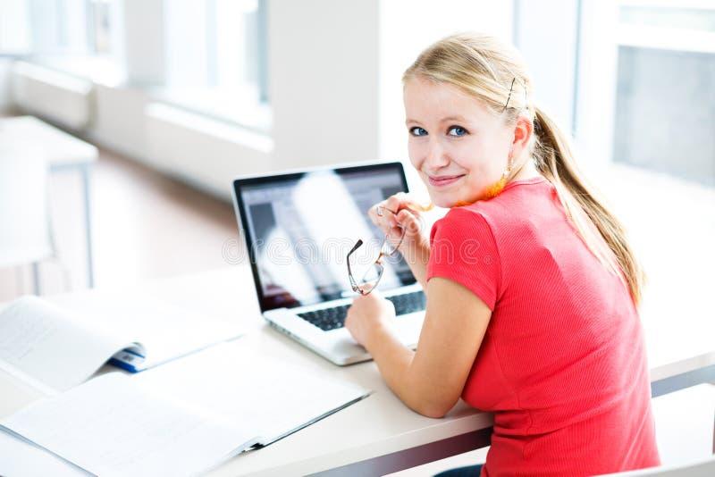 W bibliotece, żeńskim uczniu z książkami i laptopie - dosyć, obrazy stock