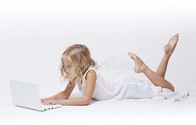 W biel piękna młoda dziewczyna, działa jej laptop obrazy stock