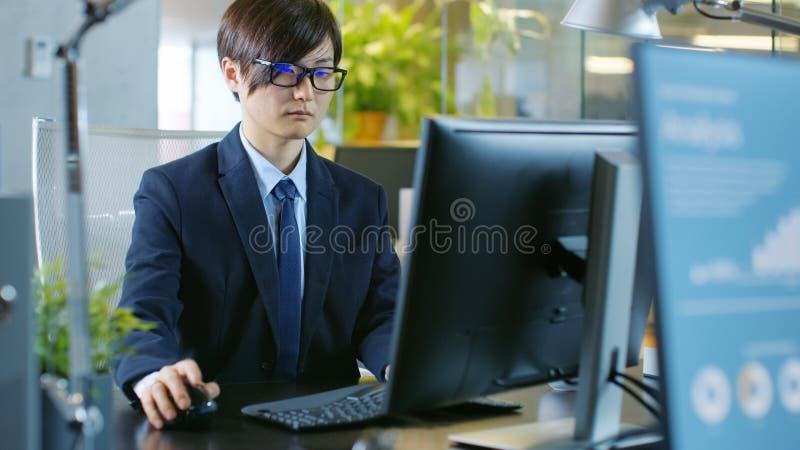 W Biurowym Wschodnio-azjatycki biznesmenie pracuje na Desktop ogłoszeniu towarzyskim obraz stock