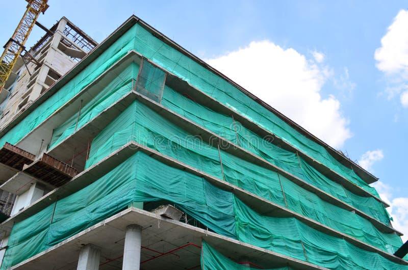 W budowie budynek zakrywający z zieleni siecią dla bezpieczeństwa zdjęcia stock