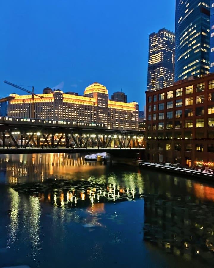 W centrum Chicago jako wieczór ustawia podczas zimy z dźwigowym budowy wyposażeniem w tle i odbicia na lodowatej wodzie, zdjęcie royalty free