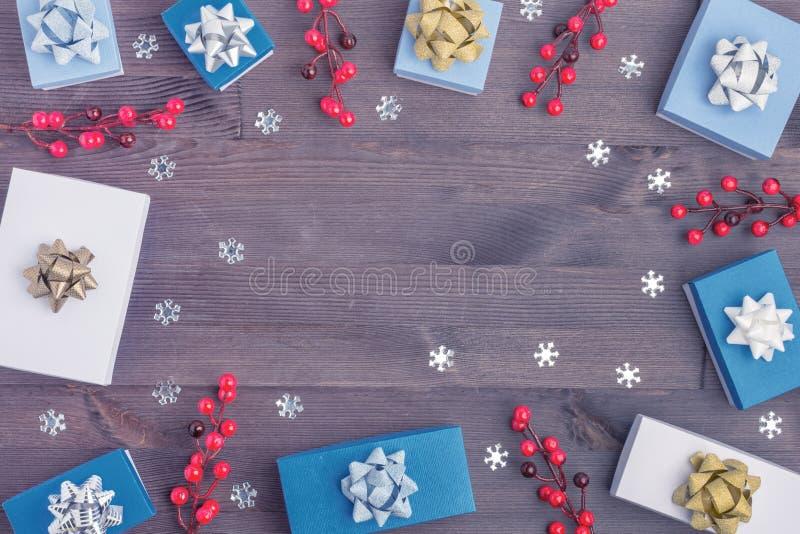 W centrum drewniana tło kopii przestrzeń Wokoło starannie rozkładający gałązki czerwone jagody, mali prezentów pudełka i zdjęcie stock