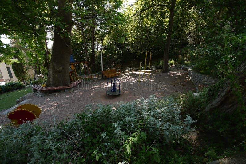 W cieniu gęstego crone zwarty klon tam jest dziecka ` s boisko z drewnianymi ławkami zdjęcie royalty free