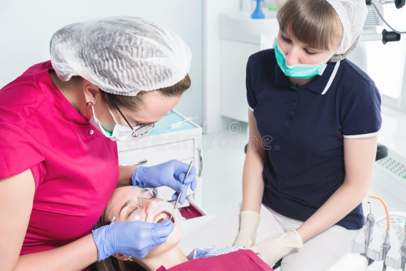W dentysty ` s biurze Egzamin oralny zagłębienie młody żeński pacjent asystentem i lekarką zapobieganie zdjęcia stock