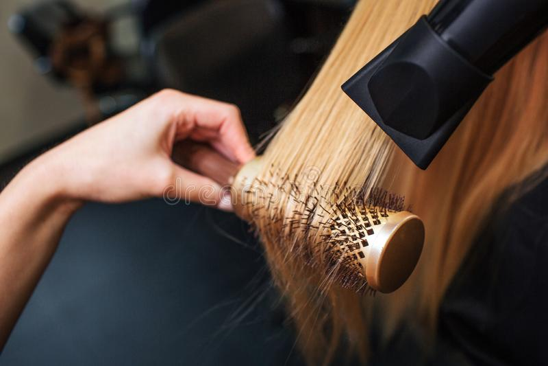 W górę fryzjerów wręcza suszarniczego blondyn z włosianą suszarką i round muśnięciem Robić fryzurze w piękno salonie fotografia stock