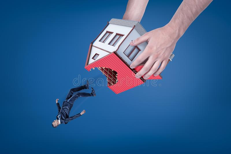 W górę mężczyzna ręk trzyma domowymi z dziurą w dachowy do góry nogami i opuszcza za małym biznesmenie zdjęcia stock