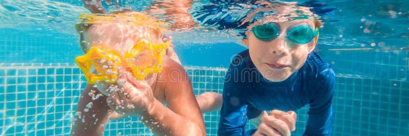 W górę podwodnego portreta dwa dzieciaków śliczny ono uśmiecha się sztandar, DŁUGI format zdjęcia stock