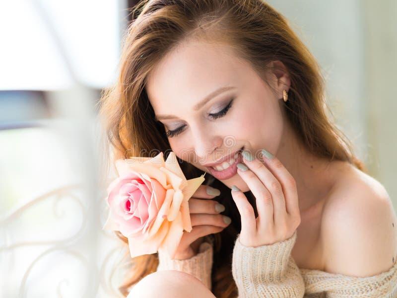 W górę portreta młody piękny kobieta uśmiechu usta z menchii róży kwiatem i dotyka jej twarz Skóry kobieta i opieka zdjęcia royalty free