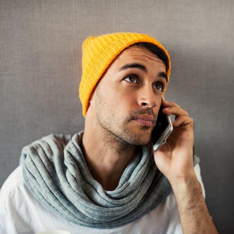 W górę portreta młody przystojny mężczyzny mówienie na telehone, będący ubranym pomarańczowego kapelusz i szarość szalika na szar obrazy royalty free