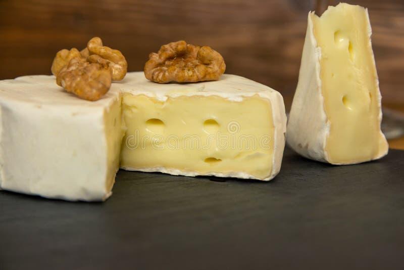 W górę siekającego camembert sera z dokrętkami na ciemnym tle zdjęcie stock