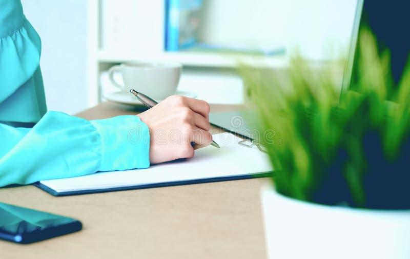W górę żeńskich ręk pisze coś w schowka obsiadaniu przy biurem zdjęcia stock