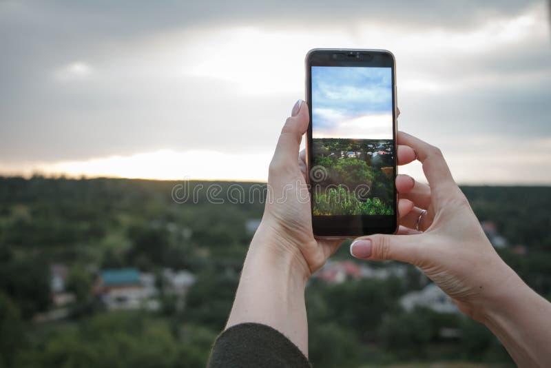 W górę żeńskich ręk strzela pięknego krajobraz z zielonymi wzgórzami i zmierzchem na smartphone, selekcyjna ostrość zdjęcie stock
