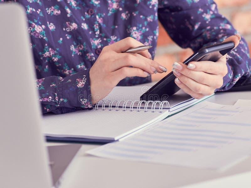 W górę żeńskich ręk używać mądrze telefon przy nowożytnym biurowym wnętrzem podczas gdy pracujący na komputerze, bizneswomanu pis zdjęcia stock