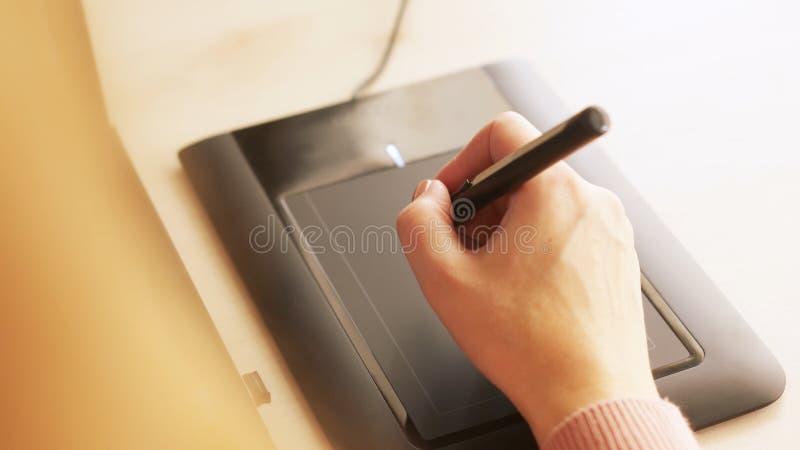 W górę żeńskiej projektant grafik komputerowych ręki używać interaktywnego pióro pokazu, cyfrowej rysunkowej pastylki i pióra na  fotografia royalty free