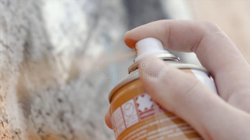 W górę artysty rysuje uliczną sztuki opryskiwania kiści farbę akcja Pobrudzeni palce artysta trzymają kiści puszkę z barwionym obrazy stock