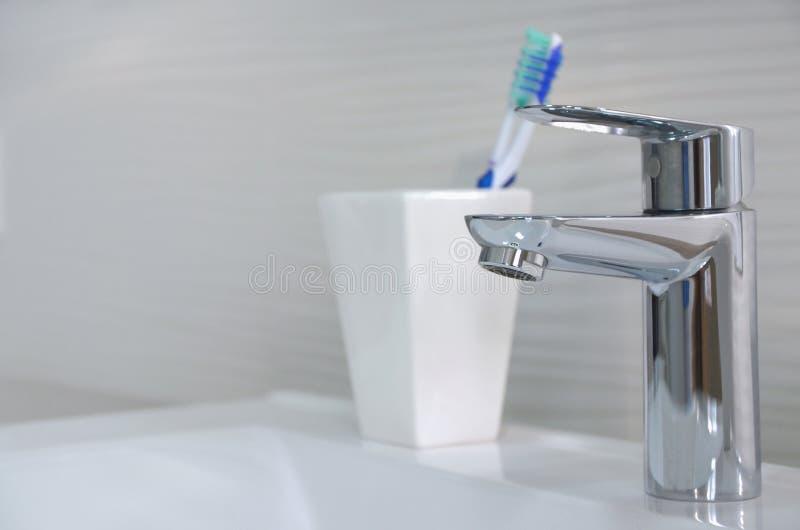 W górę błyszczącego srebnego faucet i toothbrushes w białym szkle zdjęcia stock