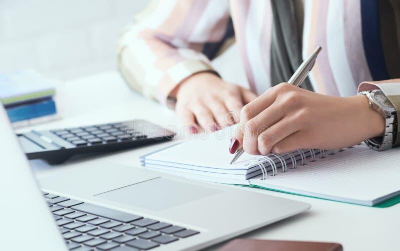 W górę biznesowej kobiety lewej ręki robi notatkom z srebnym piórem w biurze Biznes?w finansowi oszcz?dzania po?yczkowi i kredyto fotografia royalty free