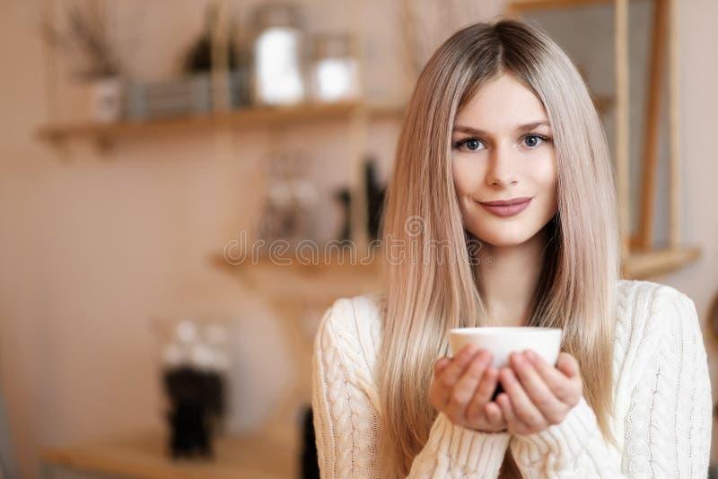 W górę blondynki dziewczyny z filiżanką gorący napój, herbata lub kawa w wygodnym pokoju, w domu obrazy stock