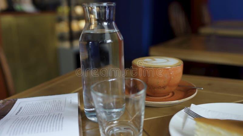 W górę butelki woda i filiżanka kawy na stole w sklepie z kawą sztuka Wygodna atmosfera przerwa na lunch w kawie obraz royalty free