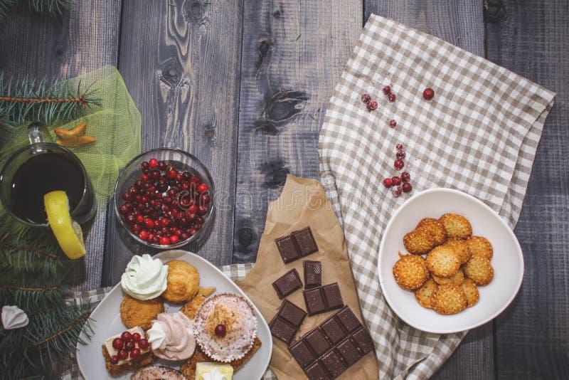 W górę cukierków na białym talerzu: kokosowy ciastko, pastila, beza, kremowe róże, Turecki zachwyt obok łamanej czekolady, zdjęcie stock