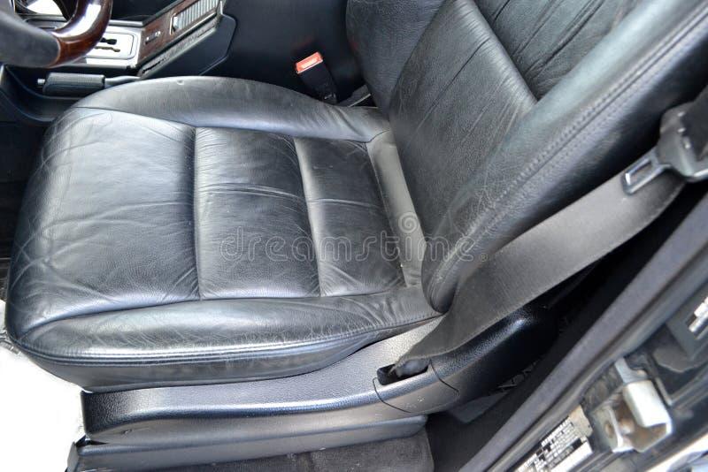 W górę frontowego starego klasycznego samochodowego siedzenia z czarnym rzemiennym podstrzyżeniem używać pojazd w złym stanie w w fotografia stock