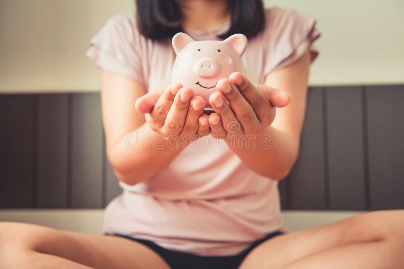 w górę kobiety ręki Trzyma prosiątko banka na sypialni, Biznesowych bankowość lub Pieniężnym pojęciu Jej, zdjęcie royalty free