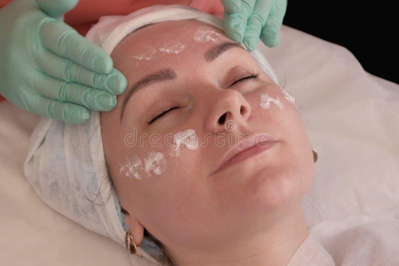 W górę kobiety twarzy i ręki beautician w rękawiczkach Beautician naciera moisturizer na kobiety twarzy Śliczna dziewczyna relaks zdjęcia royalty free