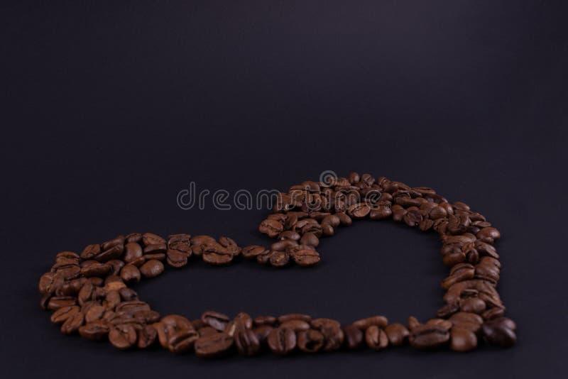W górę konturu serce kawowe fasole na zmrok powierzchni obraz royalty free