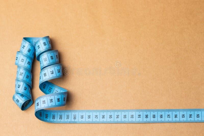 W górę krawieckiej pomiarowej taśmy na rzemiosło papieru tle Błękitnej pomiarowej taśmy płytka głębia pole zdjęcie stock