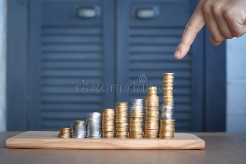 W górę a obsługuje rękę wskazuje przy kolumnami barwić monety wzrastający wzrost, pojęcie oszczędzanie i oszczędzanie pieniądze, fotografia royalty free