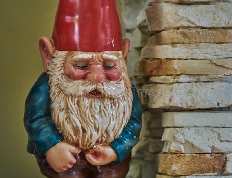 A w górę ogrodowego gnomu z czerwonym kapeluszem białą brodą i zdjęcia royalty free