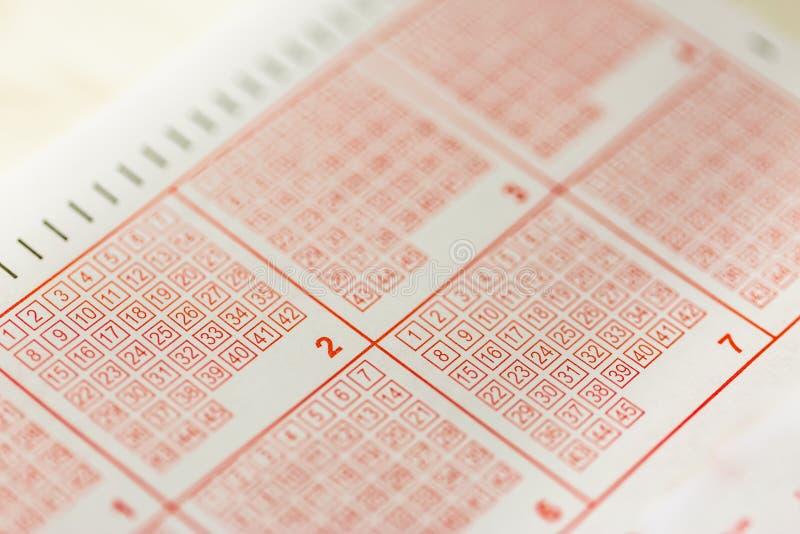 W górę osoby ręki ocechowania liczby na loteryjnym bilecie z piórem obrazy stock