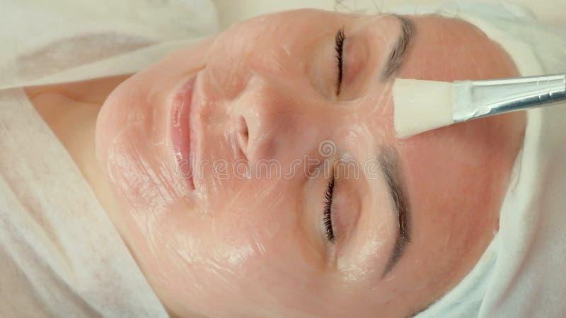 W górę pięknej dziewczyny w białym ręcznikowym lying on the beach na leżance przy zdrojem Beautician stosował z muśnięciem śmieta zdjęcia stock
