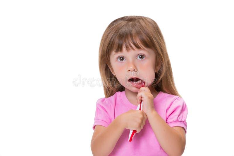 W górę portret małej dziewczynki 3 Ślicznego roczniaka w różowej koszulce szczotkuje jej zęby odizolowywających na białym tle zdjęcia stock