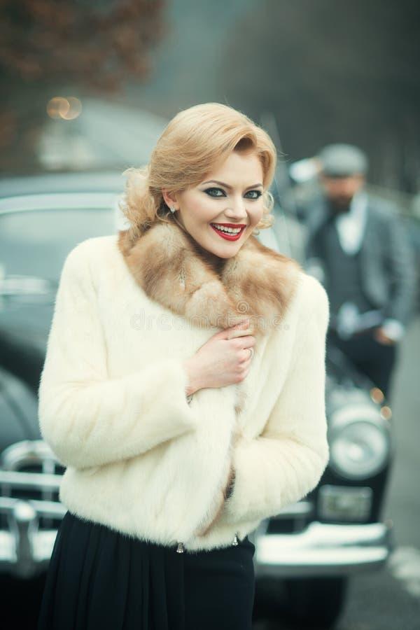 W górę portret pary młodej pięknej eleganckiej panny młodej w białym futerkowym żakiecie z fornalem w retro samochodzie na sposob fotografia royalty free