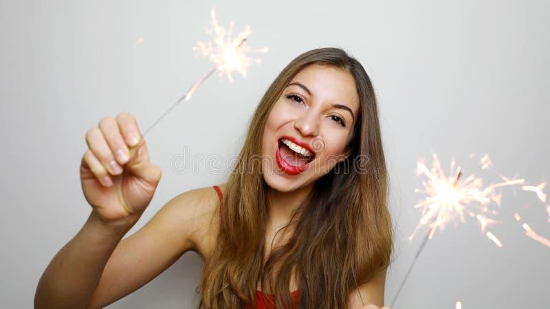 W górę portreta emocjonalni kobieta modela mienia sparklers na białym tle Roześmiana blondynki dziewczyna w czerwonym wierzchołku obrazy royalty free