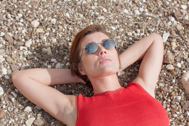 W górę portreta kobiety lying on the beach na otoczakach zdjęcia royalty free