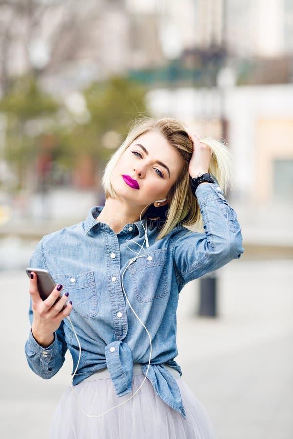 A w górę portreta marzycielska blondynki dziewczyna słucha muzyka na smartphone jest ubranym drelichową koszula z jaskrawymi różo zdjęcia stock