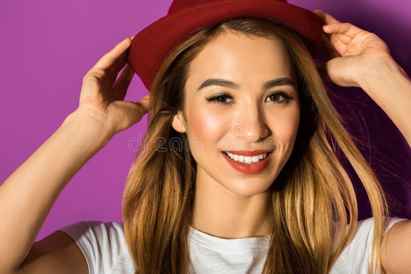 w górę portreta piękna młoda azjatykcia kobieta w kapeluszowy ono uśmiecha się przy kamerą zdjęcia royalty free