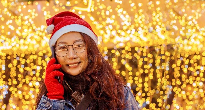 W górę portreta piękna szczęśliwa Azjatycka dziewczyna trzyma smartphone stojaki blisko Christm i świateł w czerwonym Święty Miko zdjęcie royalty free