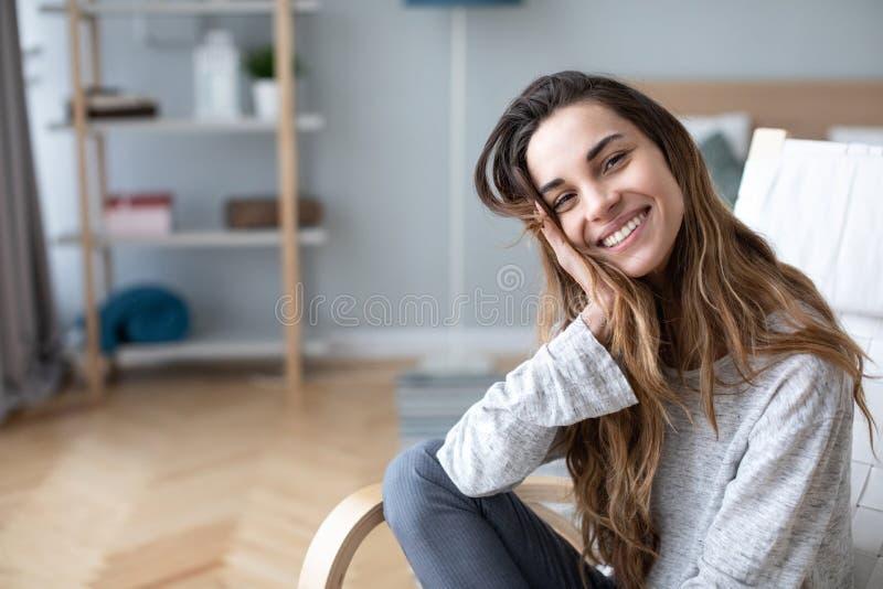 W górę portreta piękna szczęśliwa kobieta patrzeje kamerę i ono uśmiecha się podczas gdy siedzący w wygodnym krześle zdjęcia royalty free