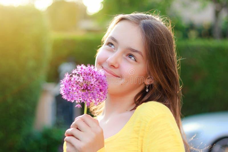 W górę portreta pięknego preteen dziewczyny mienia purpurowego allium cebulkowy kwiat w ogródzie outdoors przy zmierzchem przyglą zdjęcia royalty free