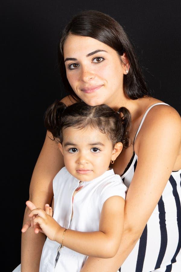 W górę portreta powabna mała dziewczynka z matką na czarnym tle zdjęcia stock