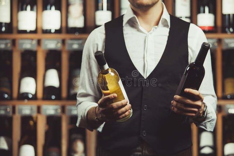 W górę portreta sommelier chwyty butelka czerwony i biały wino na lochu tle Rozmaitość alkoholiczka obrazy stock