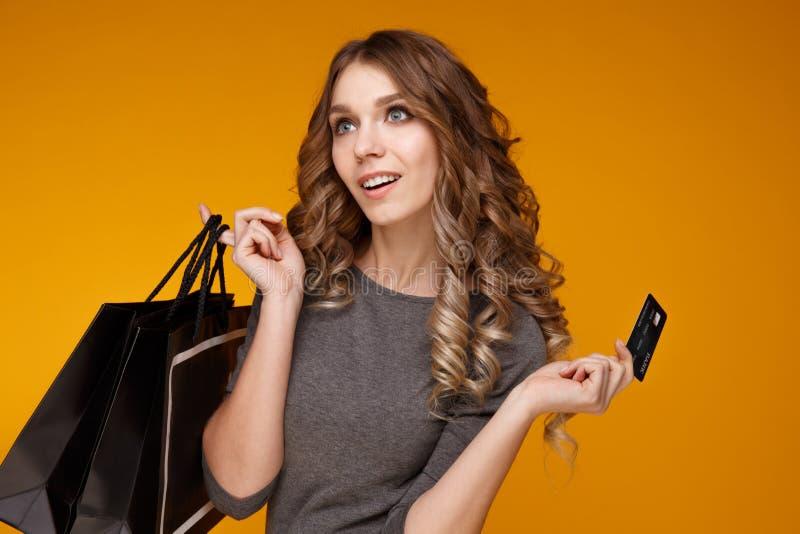 W górę portreta szczęśliwa młoda brunetki kobiety mienia karta kredytowa i kolorowe torby na zakupy, patrzeje kamerę fotografia royalty free
