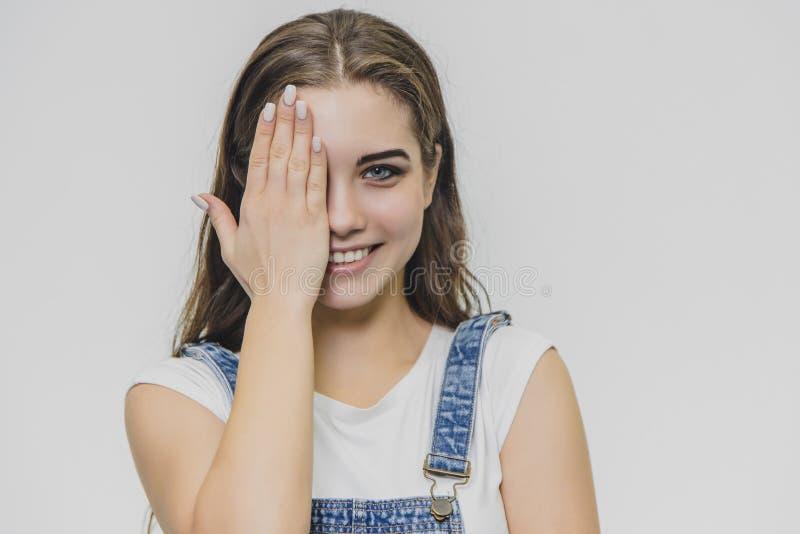 W górę portreta szczęśliwy, ładny, ufny, elegancki Uśmiechnięta dziewczyna w białej koszula Zamykający z jeden ręką pięknego obrazy royalty free