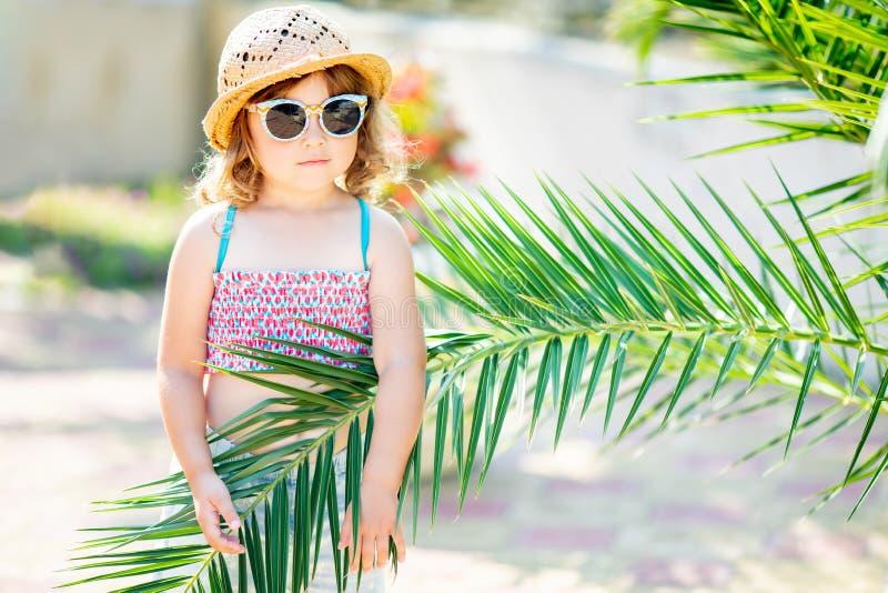W górę portreta urocza mała dziewczynka przy tropikalnym kurortem, chuje za palmą przy pogodnym letnim dniem obraz stock